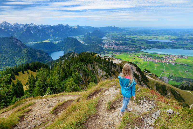 Cute little hiker enjoying picturesque views from the Tegelberg mountain, a part of Ammergau Alps, located nead Fussen town, Germa stock photo