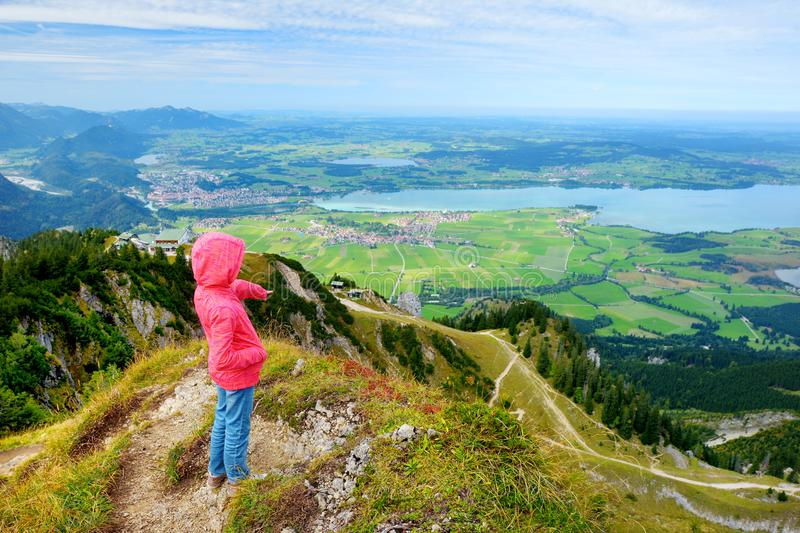 Cute little hiker enjoying picturesque views from the Tegelberg mountain, a part of Ammergau Alps, located nead Fussen town, Germa stock image