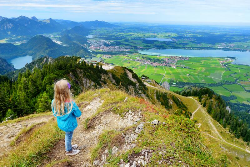 Cute little hiker enjoying picturesque views from the Tegelberg mountain, a part of Ammergau Alps, located nead Fussen town, Germa stock photography