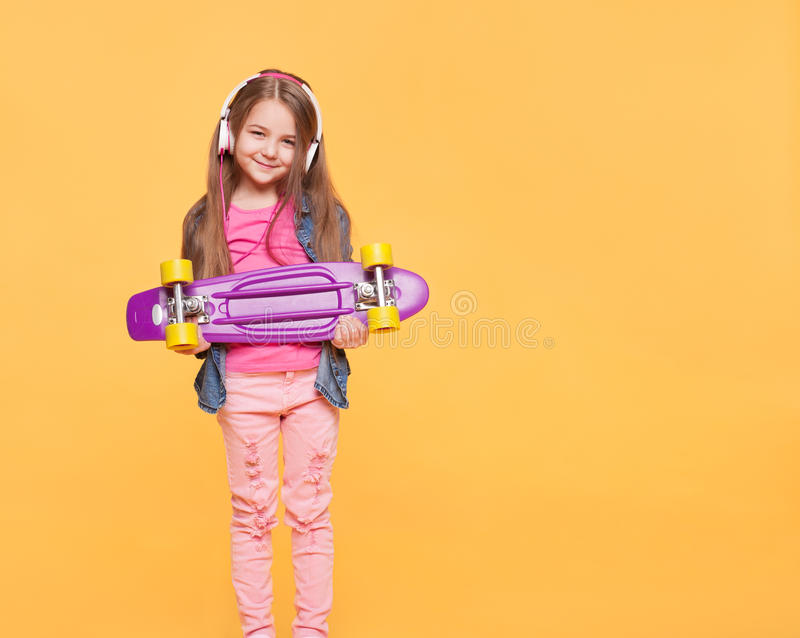 Cute little hipster girl with headphones and skateboard stock image
