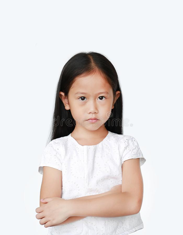 Cute little hispanic Asian child girl with arms crossed and angry about something over white background with looking at camera. royalty free stock image