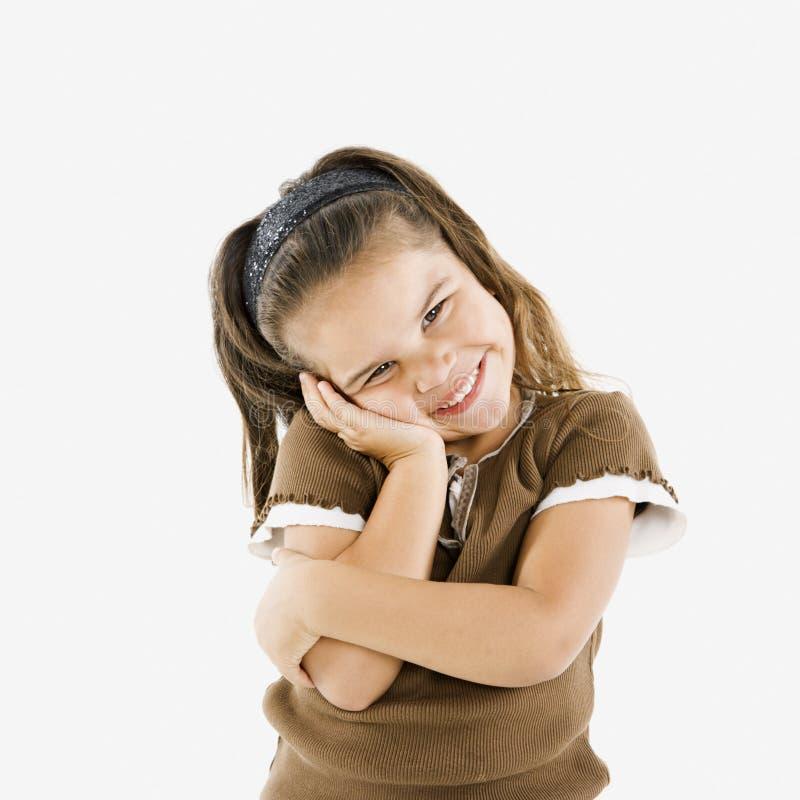 Cute little hispanic girl. Adorable little hispanic girl standing smiling with cheek in hand stock photography