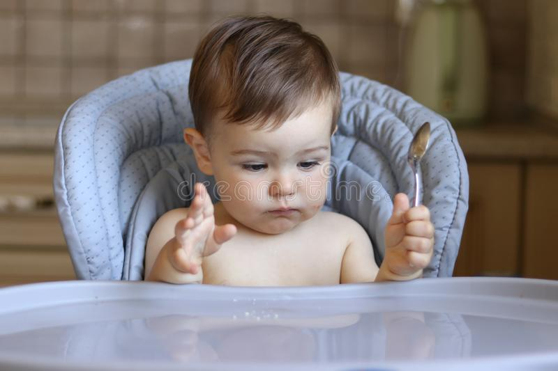 Cute little hungry baby boy holds spoon in his hand and looks at empty table waiting for food royalty free stock photos