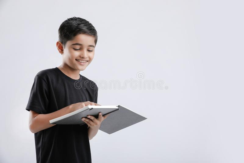 Cute little Indian / Asian boy reading book isolated over white background stock photography