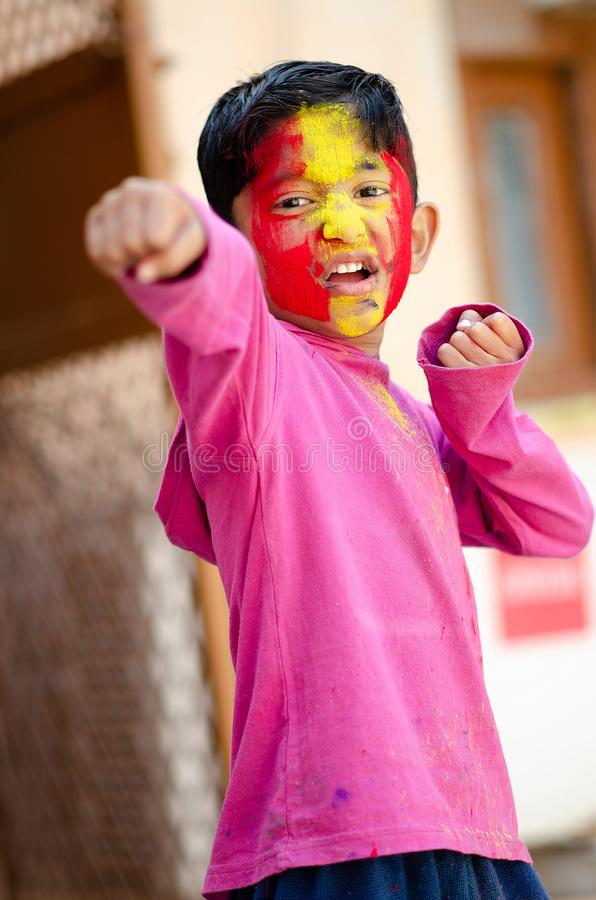 Cute Little Indian boy child boxing with coloured face during holi indian festival looking at camera. Cute Little Indian boy child boxing showing punch with stock images