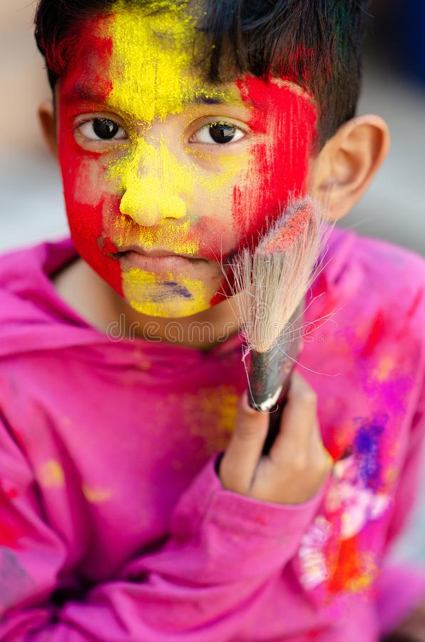 Cute Little Indian boy child with coloured face holding paint brush during holi indian festival looking at camera. Cute Little Indian boy child with coloured stock photography