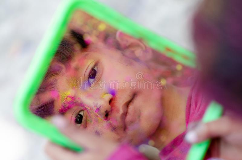 Cute Little Indian boy child with coloured face paint looking in mirror. Reflection portrait royalty free stock photography
