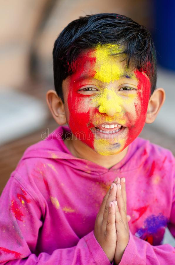 Cute Little Indian boy child welcome namste pose with coloured face during holi indian festival looking at camera. Cute Little Indian boy child welcome namste stock photo