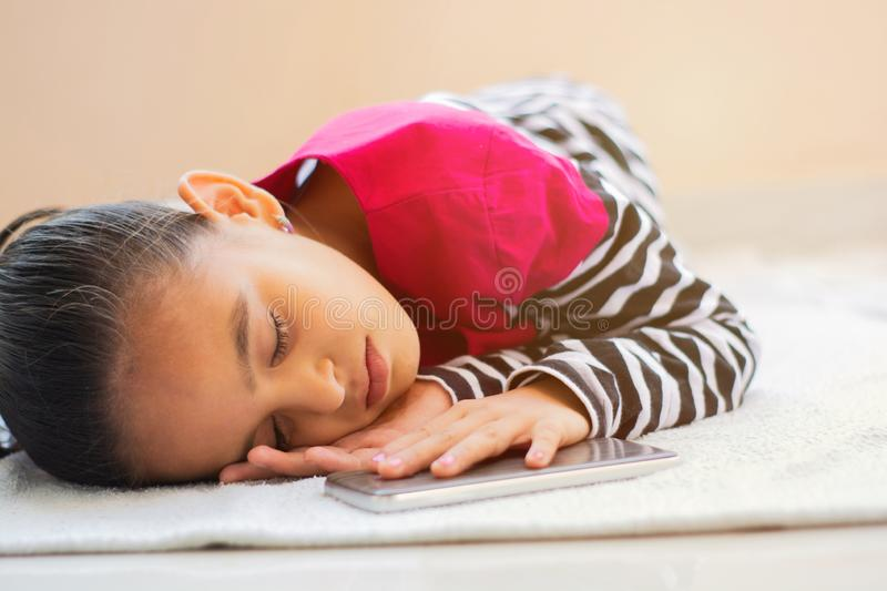 Cute Little Indian girl kid slept with mobile phone next to her on bed.  stock photo