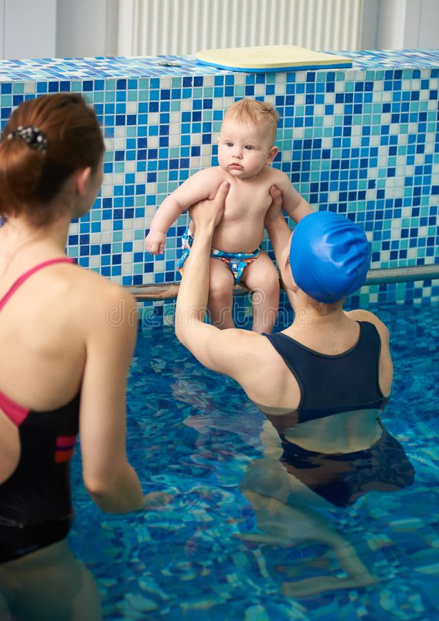 Cute little infant resting in pool. Two women instructor and young mother preparing baby for first swimming and diving royalty free stock photo