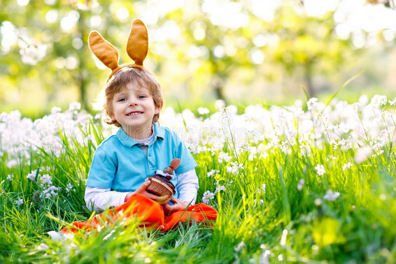 Cute little kid boy with Easter bunny ears celebrating traditional feast. Happy child eating chocolate cake of muffin on royalty free stock photography