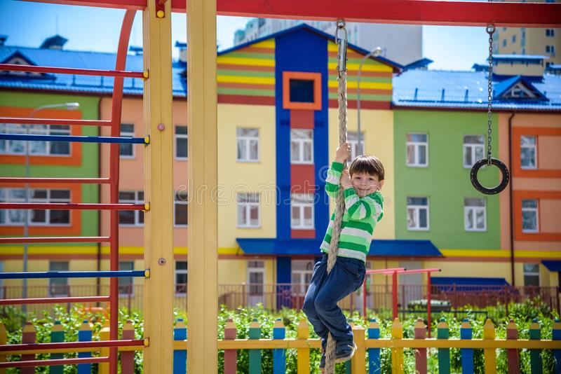 Cute little kid boy enjoying climbing rope on a playground. Toddler child learning to climb, having fun on warm sunny spring day. stock image