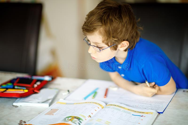 Cute little kid boy with glasses at home making homework, writing letters with colorful pens. Little child doing exercise, indoors. Elementary school and stock photo