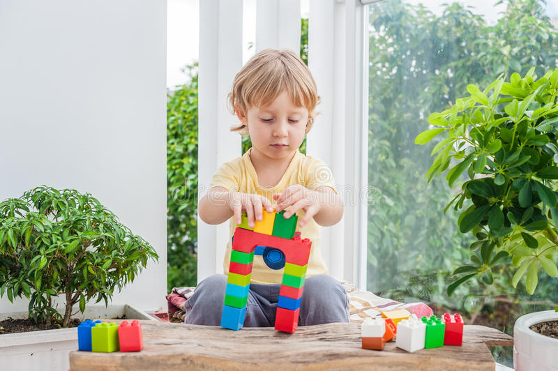 Cute little kid boy with playing with lots of colorful plastic blocks indoor. Active child having fun with building and creating o stock photos