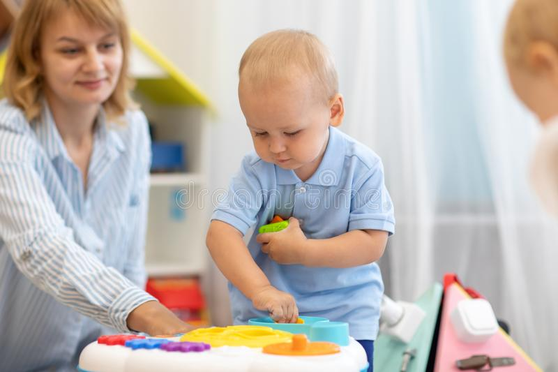 Cute little kid playing with toys in nursery group of kindergarten royalty free stock images