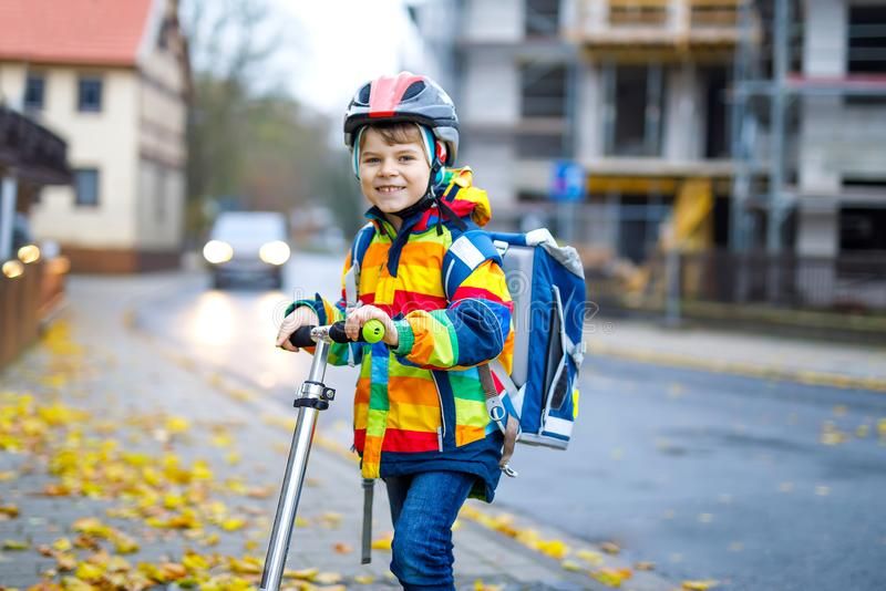Cute little kid boy riding on scooter on way to school. Cute little school kid boy riding on scooter on way to elementary school. Child with safety helmet stock photography
