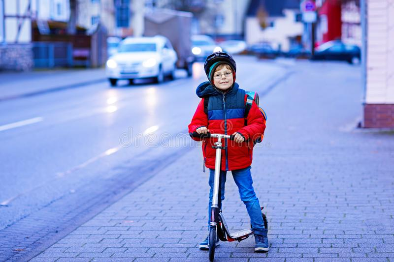 Cute little kid boy riding on scooter on way to school. Cute little school kid boy riding on scooter on way to elementary school. Child with safety helmet royalty free stock photo