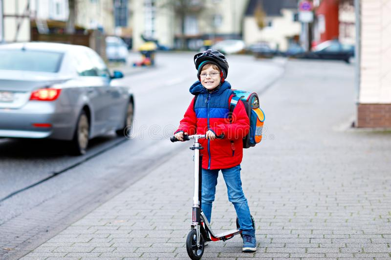 Cute little kid boy riding on scooter on way to school. Cute little school kid boy riding on scooter on way to elementary school. Child with safety helmet royalty free stock image