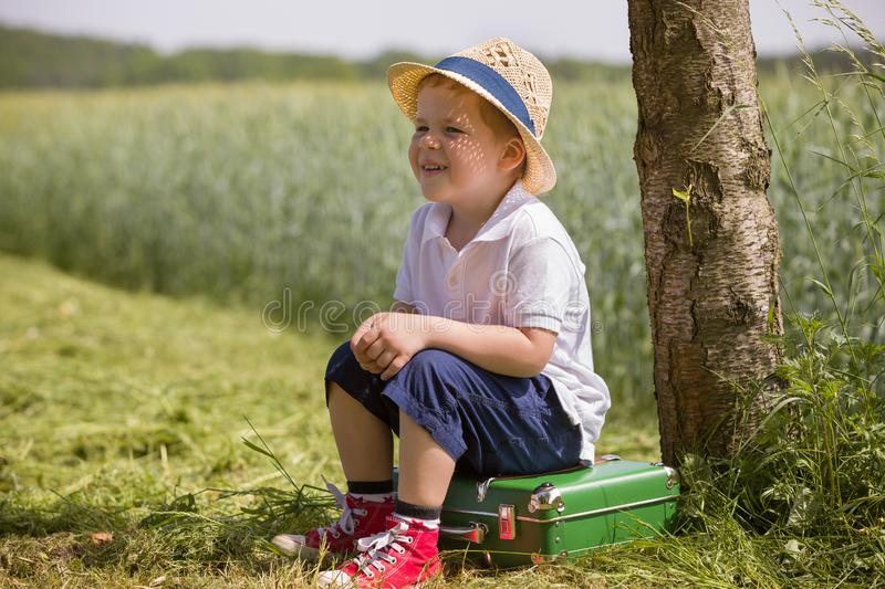 Cute little kid boy in shorts, white polo and straw hat sits on his green suitcase in a field and waiting for a bus royalty free stock photos