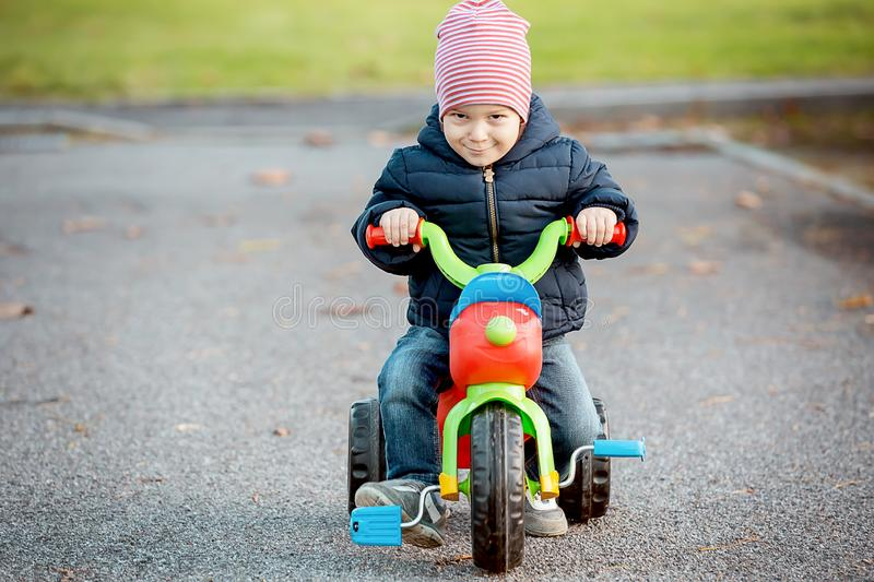 Cute little kid boy in warm autumn clothes having fun with tricycle stock photo