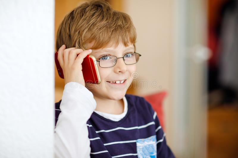 Cute little kid boy wearing eye glasses speaking on cellular phone. Adorable healthy child holding smartphone and stock photos
