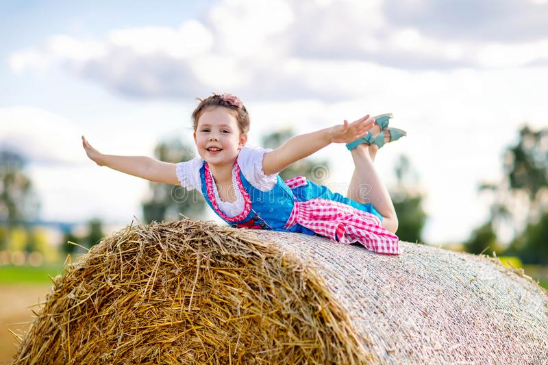 Cute little kid girl in traditional Bavarian costume in wheat field. German child with hay bale during Oktoberfest in Munich. Preschool girl play at hay bales stock photography