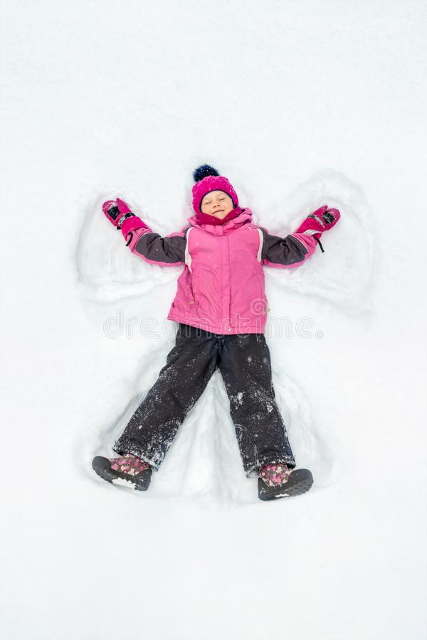 Cute little kid girl in warm ski sport suit making snow angel outdoors. Kid having fun lying on snowdrift after snow royalty free stock image
