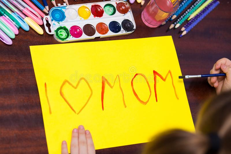 Cute little kid girl writes the text `I love mom` by paints stock photos