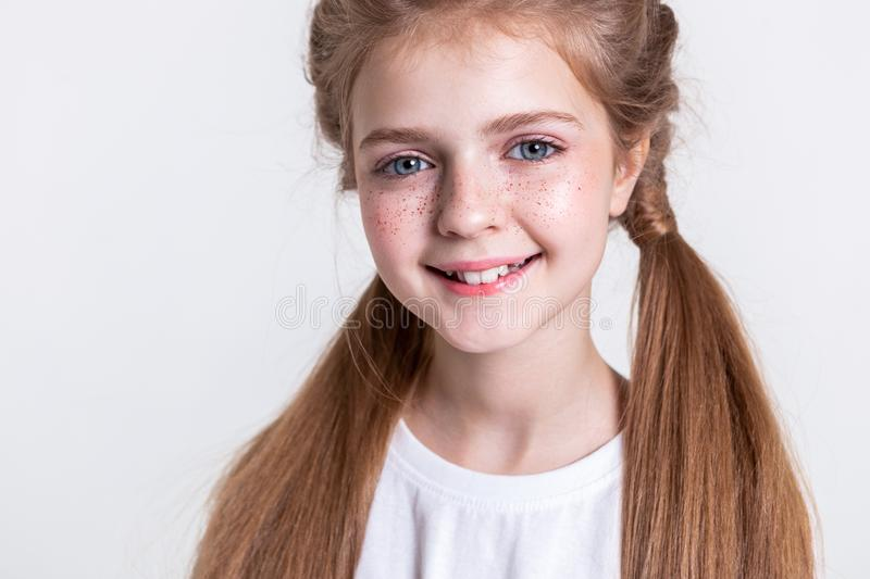 Cute little kid with long light hair and bunch of freckles. Smiling on camera. Cute little kid with long light hair and bunch of freckles showing her teeth while stock photo