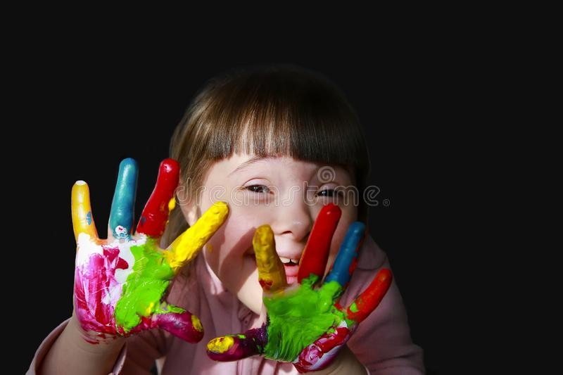 Cute little kid with painted hands isolated on the black.  royalty free stock image