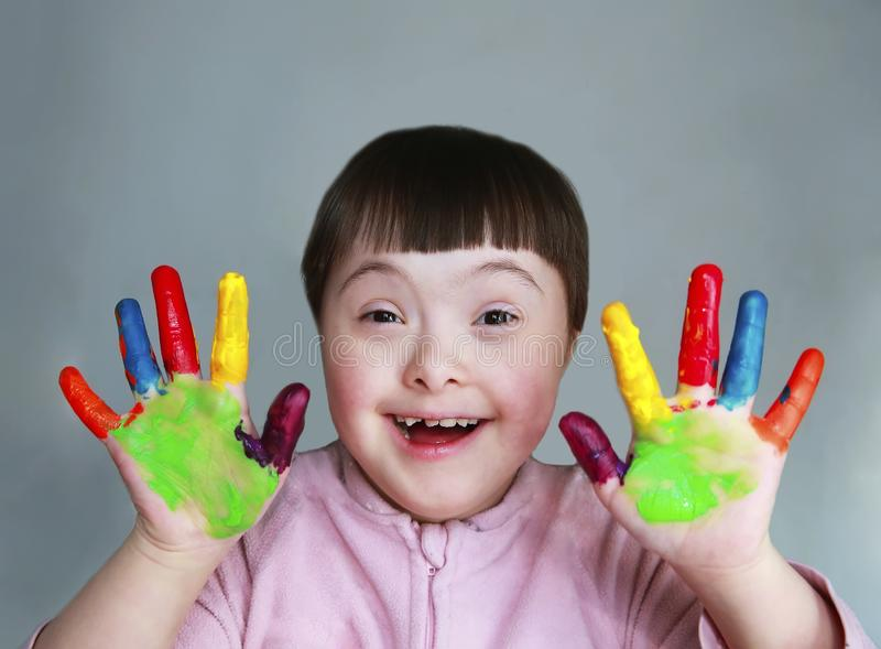 Cute little kid with painted hands. Isolated on grey background.  royalty free stock photography