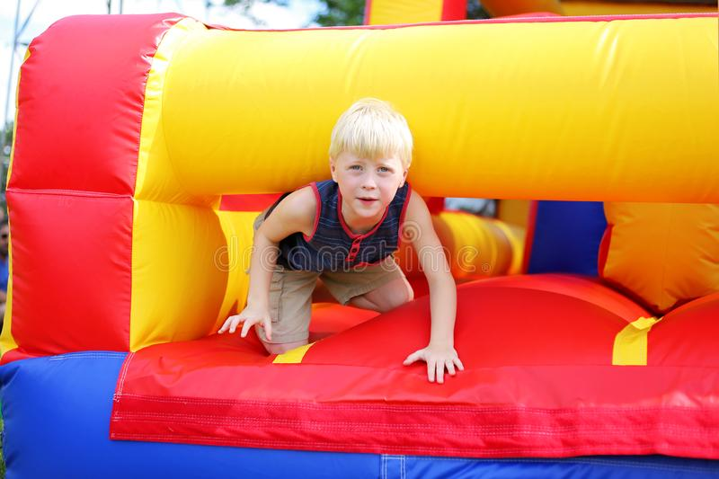 Cute Little Kid Playing on Inflatable Bounce House Obstacle Course at American Festival. A cute little kid is playing on an inflatable bounce house obstacle stock image