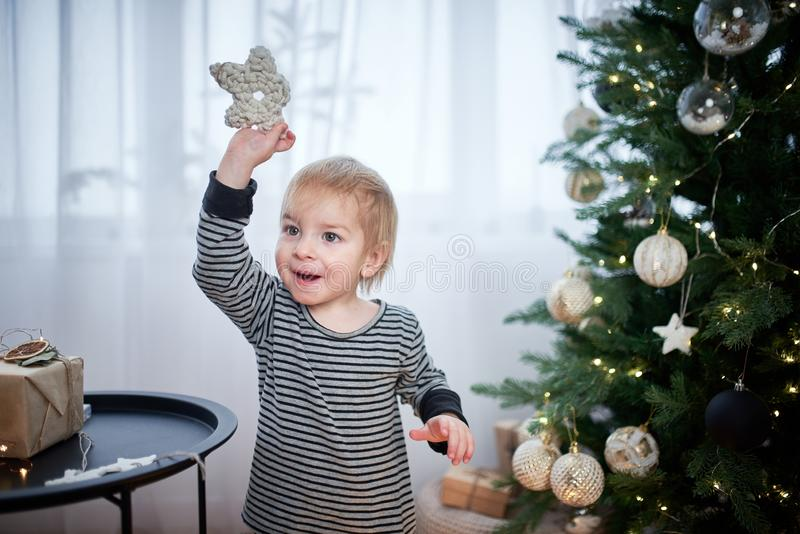 Cute little kid playing in the room. Christmas tree with lights on a background stock photo