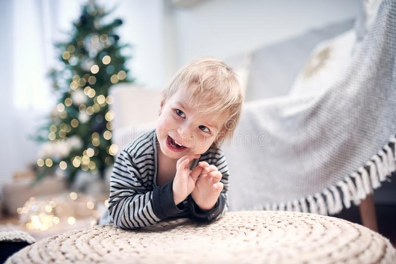 Cute little kid playing in the room. Christmas tree with lights on a background stock photos