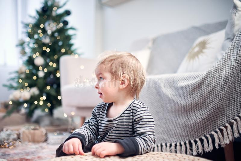 Cute little kid playing in the room. Christmas tree with lights on a background stock image