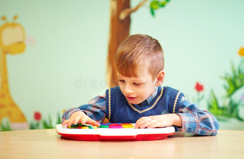 Cute little kid with special needs playing in rehabilitation kindergarten. Cute little boy, kid with special needs playing in rehabilitation kindergarten stock image