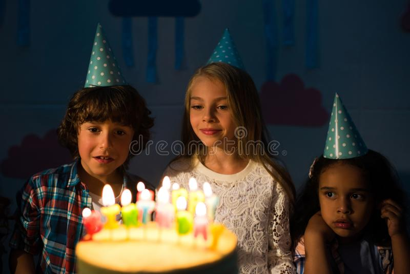 Cute little kids looking at birthday cake with burning candles. In dark room stock image