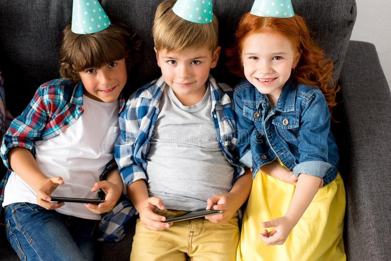 cute little kids in party caps using smartphones while sitting on sofa and smiling stock images