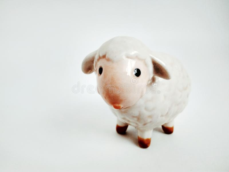 Cute little lamb statuette on white close up. Little lamb statuette on white close up stock photo