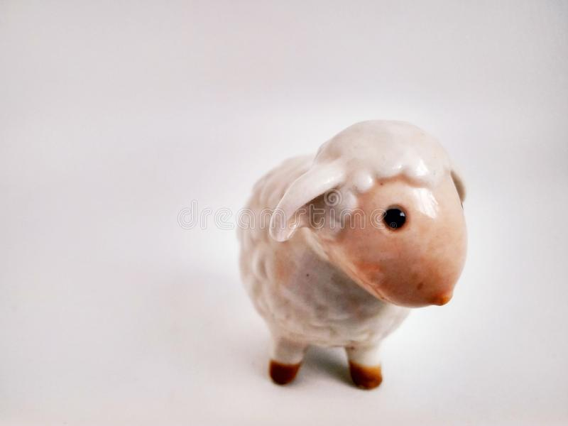 Cute little lamb statuette on white close up. Little lamb statuette on white close up stock photos