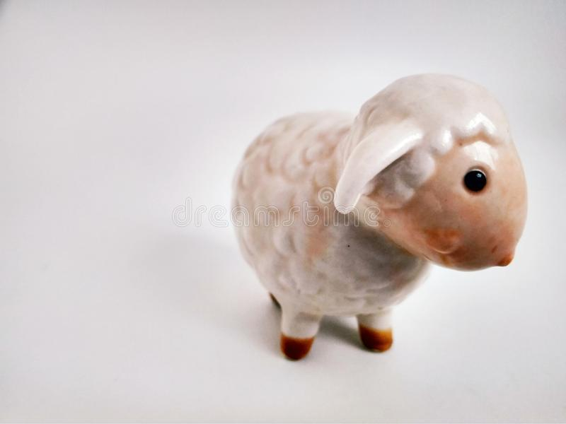 Cute little lamb statuette on white close up. Little lamb statuette on white close up royalty free stock photos