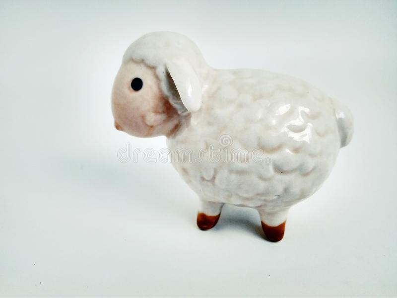 Cute little lamb statuette on white close up. Little lamb statuette on white close up royalty free stock photo