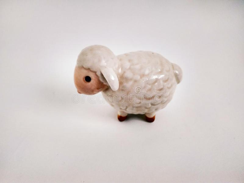 Cute little lamb statuette on white close up. Little lamb statuette on white close up royalty free stock images