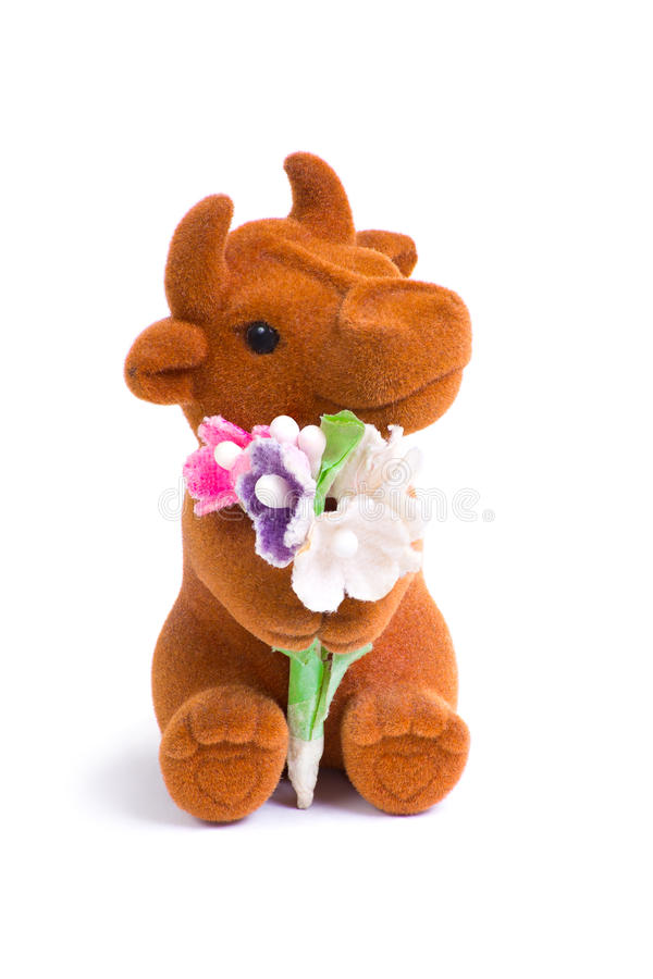 Cute little loved bull toy with bouquet of flowers. Front macro shot of cute little loved bull toy with bouquet of flowers stock images