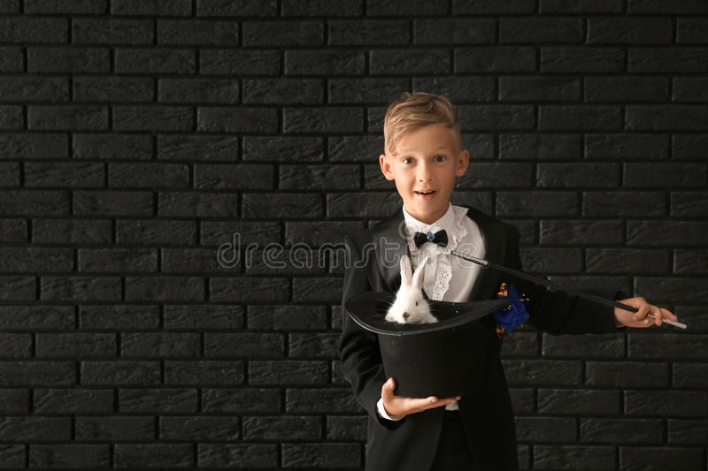 Cute little magician holding hat with rabbit against dark brick wall stock photography