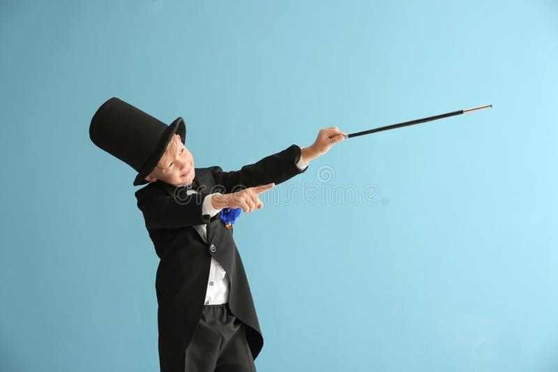Cute little magician showing trick on color background royalty free stock photography