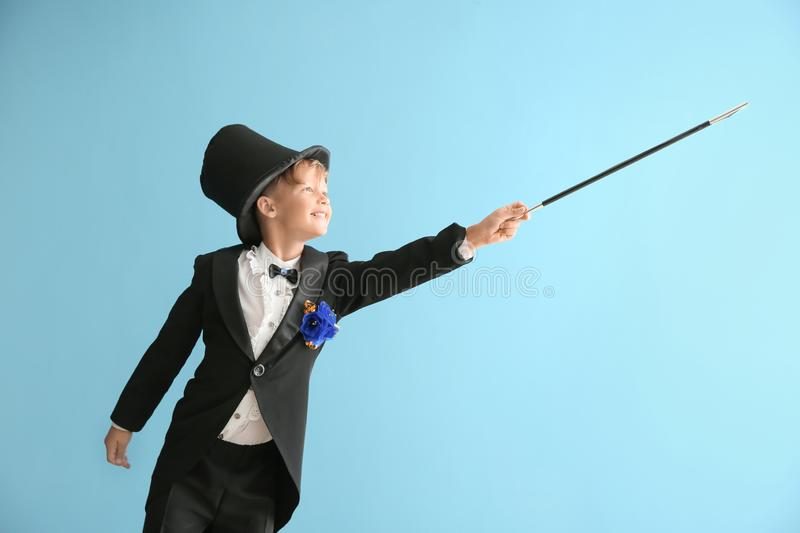 Cute little magician showing trick on color background stock photography