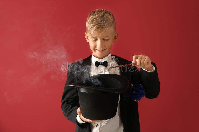 Cute little magician showing trick with hat on color background stock images