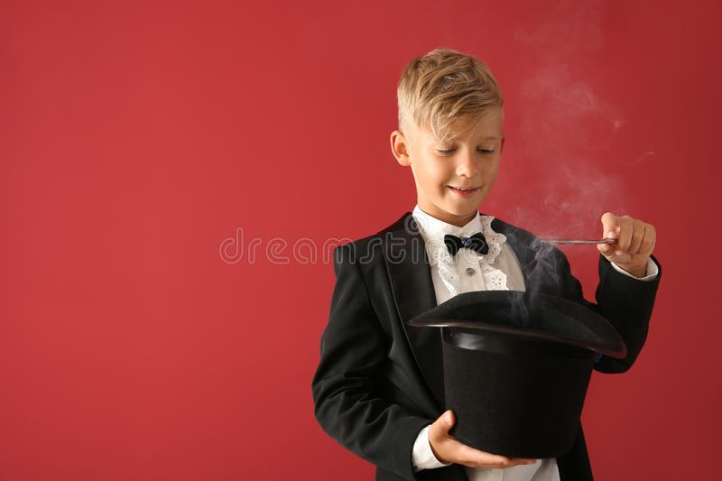 Cute little magician showing trick with hat on color background royalty free stock image