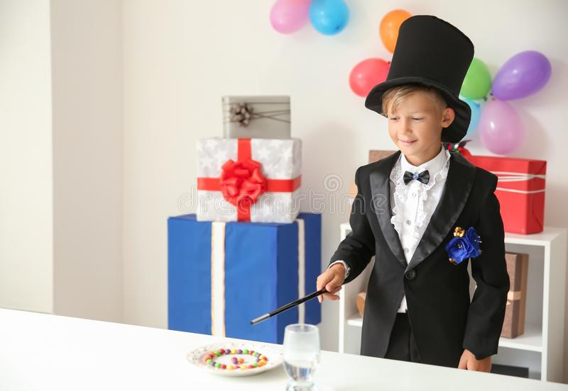 Cute little magician showing trick indoors royalty free stock photos
